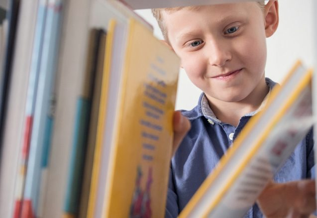 A picture of a boy taking a book off a shelf.