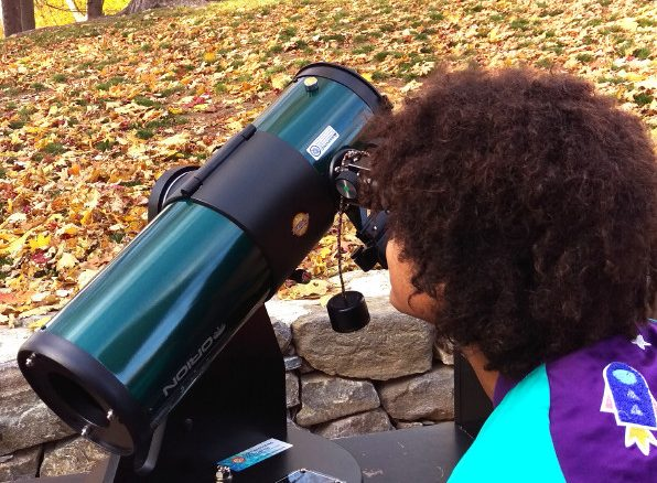 A picture of a child and a telescope.