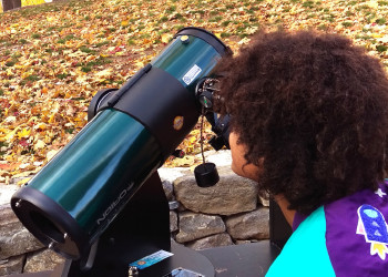 A picture of a kid and a telescope.