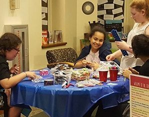 Teens sitting around a table doing a craft