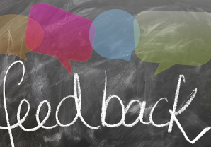 the word feedback on a chalkboard with colored speech bubbles above it