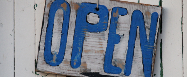 Blue and White Open sign on side of barn