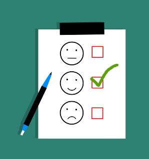 Three smiley faces on a piece of paper with checkboxes next to them and a checkmark in the middle smiling one