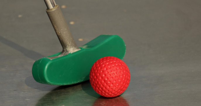green putter next to an orange mini golf ball