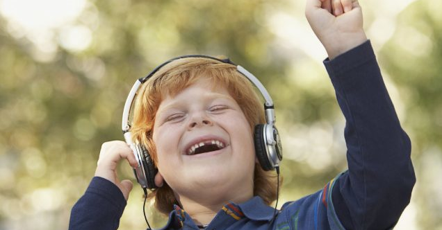 Kid with headphones on smiling and having fun