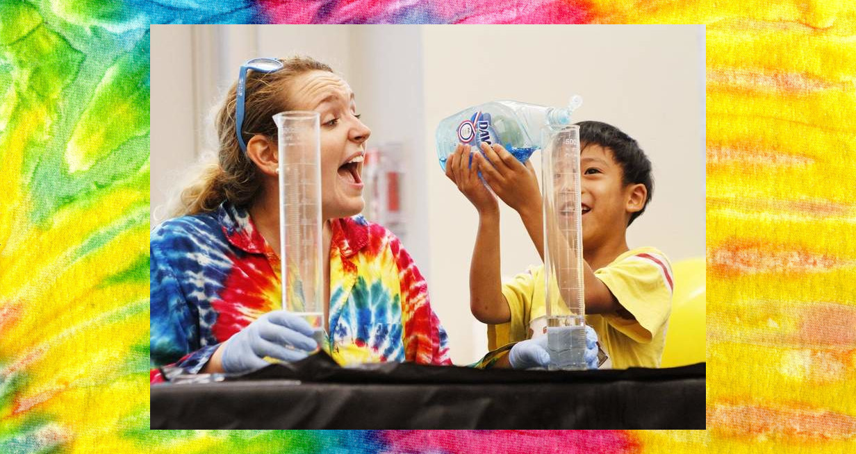 Picture of Woman laughing with boy putting dish soap into a graduated cylinder on a Tie Dye background
