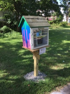 Little Free Library with side painted as dripping paint in green, blue, purple, and pink