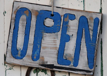 Blue open sign on the side of a white barn