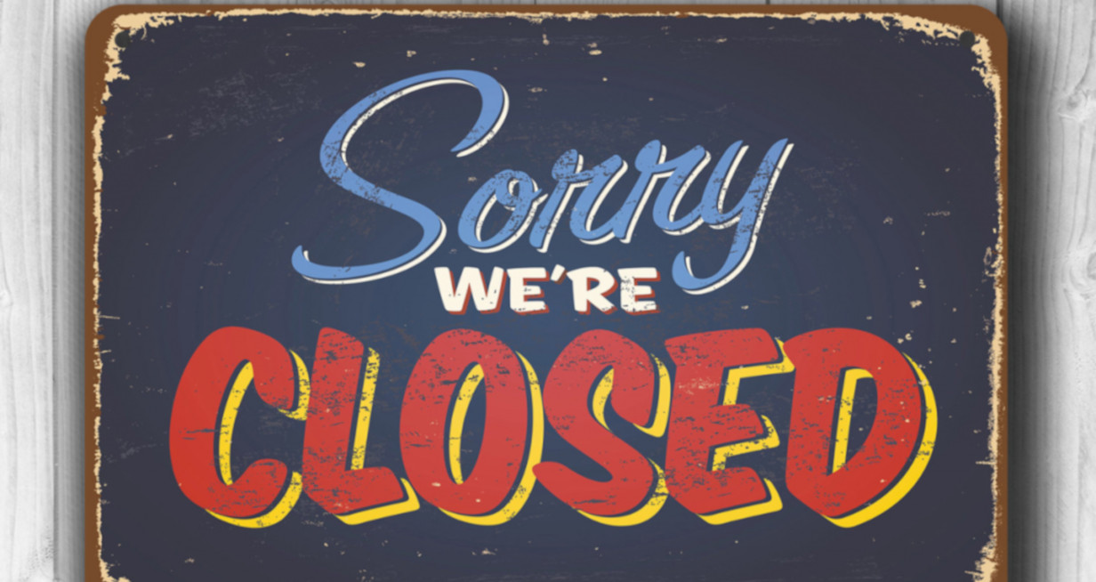 Blue worn out looking sign that says Sorry We're Closed. With the word closed in red letters with a yellow drop shadow