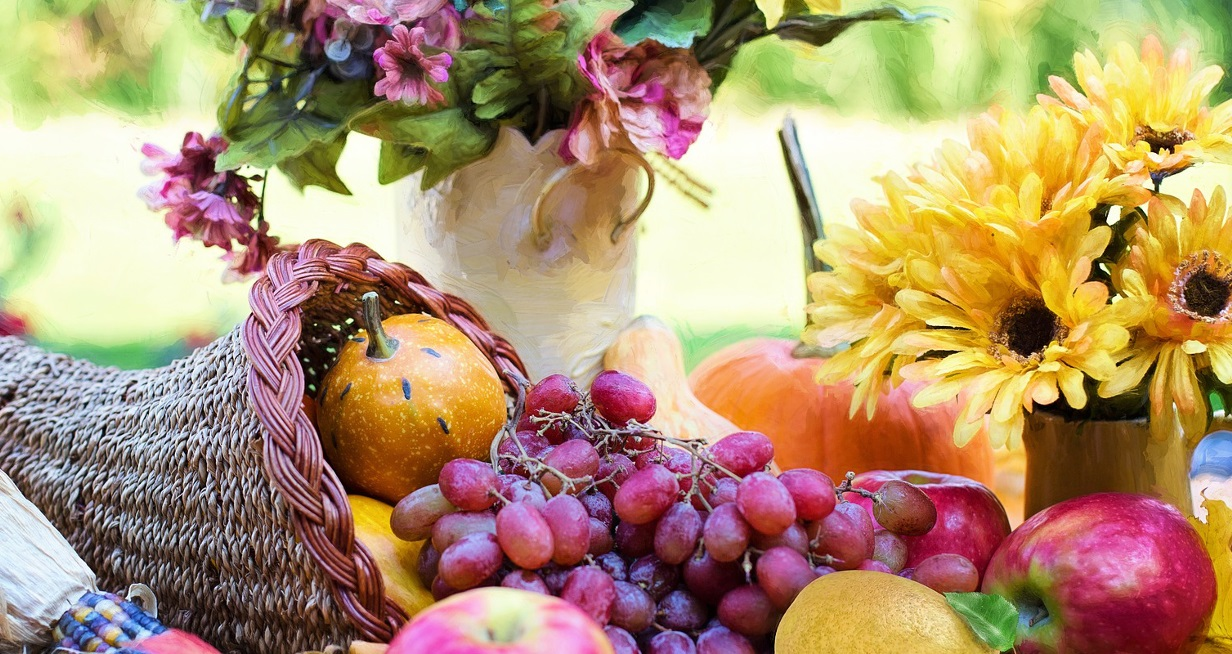 Cornocopia basket with gourds, apples, and grapes in it and a pitcher of yellow flowers next to it
